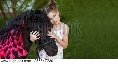 Cute Little Girl And Black Pony In A Beautiful Park. Pretty Girl Embracing  A Pony. Spring Or Summer