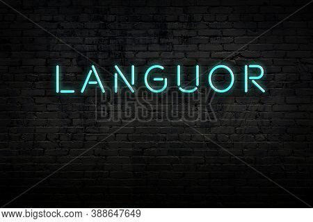 Neon Sign With Inscription Languor Against Brick Wall. Night View