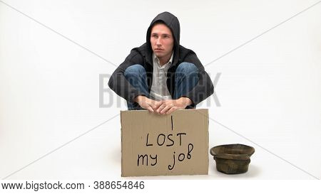 Young Jobless Man With Cardboard Sign. I Lost My Job. Man Sits And Begs For Money Isolated On White