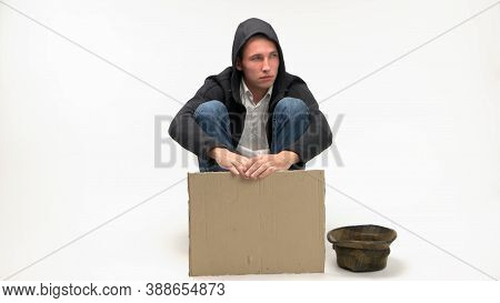 Copy Space Job Loss And Financial Crisis Concept. Jobless Young Man With Blank Cardboard For Copy Sp