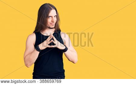 Young adult man with long hair wearing goth style with black clothes hands together and fingers crossed smiling relaxed and cheerful. success and optimistic