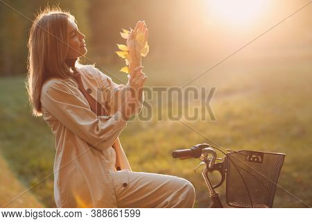 Happy Young Woman Holds Fall Leaves In Hand And Ride Bicycle In Autumn Park