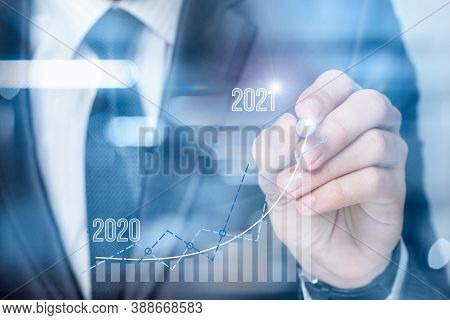The Concept Of Planning A Successful 2021. Businessman Draws A Graph Of Financial Growth And Numbers