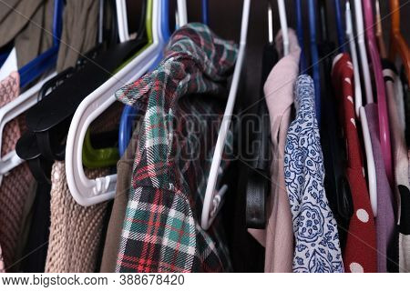 Unorganized Clothes Of Different Colors Hanging In A Wardrobe In Mess Close Up, Storage And Order At