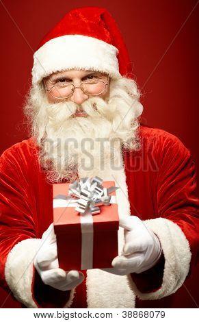 Photo of kind Santa Claus giving xmas present and looking at camera
