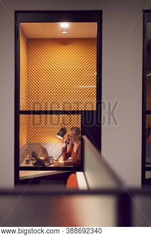 Businesswoman Working Late In Individual Office Cubicle On The Phone Using Laptop