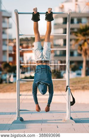 Man Hanging Upside Down On The Horizontal Bar In Anti Gravity Or Inversion Boots. Sports Equipment.b