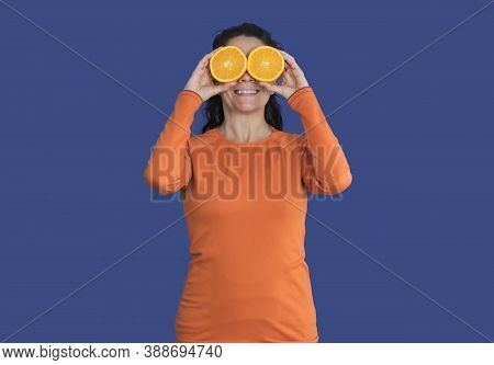 Brunette Woman With Oranges On Her Face, Wearing Orange T-shirt Isolated On A Pantene Blue Backgroun