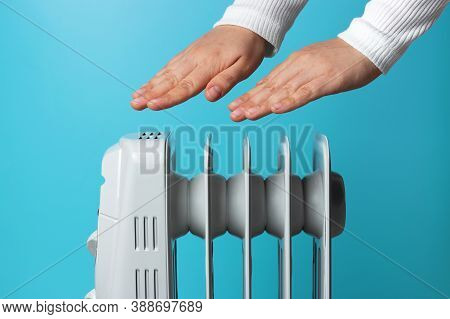 Female Hands Warm Up Near The Heater On Blue Background