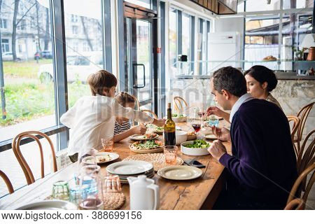 A Family Of Four Are Having Lunch On A Spacious Porch.