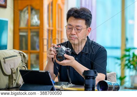 A Middle-aged Asian Man Whose Hobby Is 35Mm/135Mm Film Slr Camera.