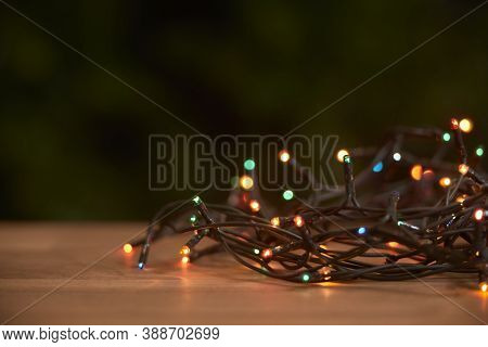 Christmas Scene: Lighted Light Cord With Different Colored Lights Shining On A Wooden Surface