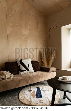 Stylish Living  Corner With Velvet Tan Color Sofa Setting With Soft Pillows With Plywood Wall On The