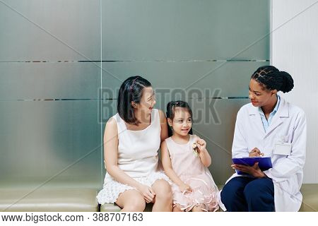 Smiling Friendly Young Black Pediatrician Talking To Little Girl And Her Mother
