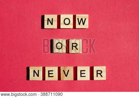 Now Or Never - The Motivating Inscription Is Laid Out On A Red Background With Wooden Blocks With Bl