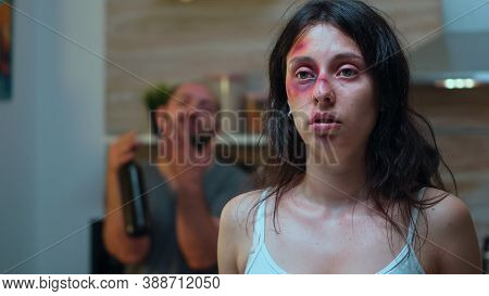 Hurt Woman And Drunk Man Holding A Bottle Of Wine Sitting In The Kitchen. Violent Aggressive Husband