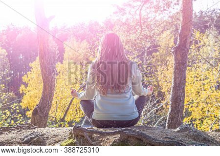 Young Woman Backpacker, Sit On Top Rock And Meditates In Lotus Position (padmassana), Back View. Yog