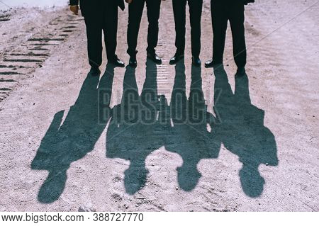 Shadow Of A Group Of Faceless People In Black Suits On A Bright Sunny Day On The Sand.