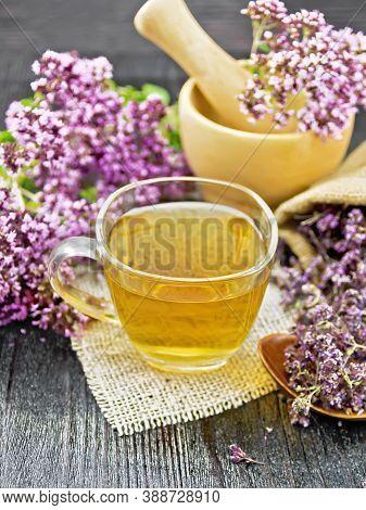 Tea Of Oregano In Cup With Mortar On Dark Wooden Board