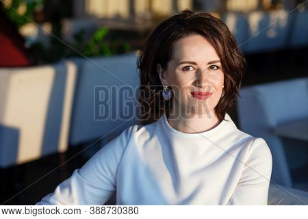 Portrait Of Happy Beautiful Lady In A Light Dress At A Coffee Shop. Successful Mature Woman Smiling