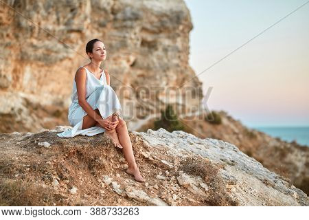 Attractive Female In Dress Dreaming Sitting On Rock. Time Alone Self Absorbed And Contemplation Natu