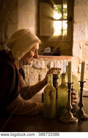 Woman in medieval outfit working as an alchemist or witch in the kitchen of a French medieval castle