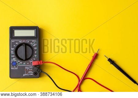 Digital Multimeter With Probes And Backlit Display On A Yellow Background. A Multimeter Or A Multite