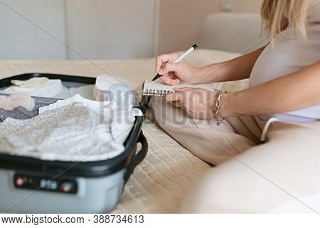 Young Pregnant Woman Packing Suitcase For Maternity Hospital At Home, Closeup. Checklist For Childbi