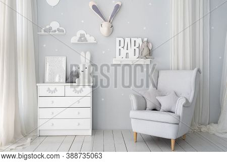 Kids Playroom With White Wooden Commode, Bunny Toys, Picture Frame, Star Pillows On Comfort Armchair