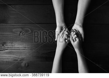 Top View Arms Stretches Out And Holds One Another On Black Wooden Background. Joint Support And Assi