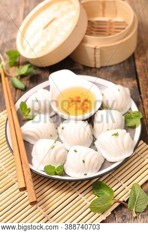 traditional chinese steamed dumplings dim sums in bamboo steamer and chopsticks