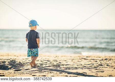 Toddler Boy Walking On A Sunny Beach. Little Child Walking On Sand. Beautiful Inspirational Beach An