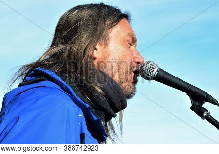 Livigno, Italy, January 18, 2019: Portrait Of A Rock Singer Performing In A Blue Winter Jaket In The