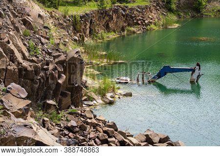 Drowned In Flooded Basalt Quarry Excavator. Summer Basalt Pillars Geological Reserve And Basaltove L
