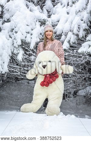 Smiling Happy Woman Out In The Snow With A Large Soft Toy