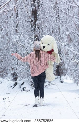 Woman Standing In The Snow Covered Pine Forest In Winter With Snow Falling All Around Her.  She Is W