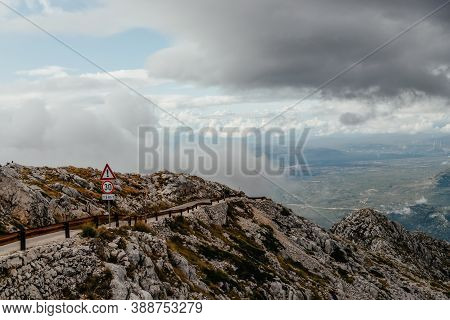 Biokovo. Mountain Landscape With Low Clouds. Warning Road Sign With Exclamation Mark And 30 Mph Spee