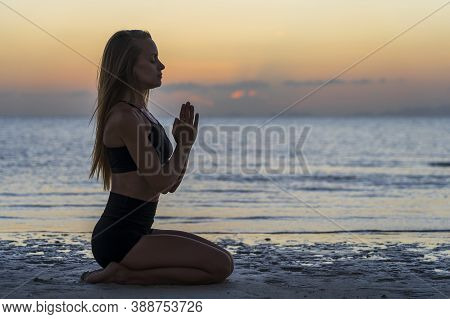 Silhouette Of Woman Sitting At Yoga Pose On The Tropical Beach During Sunset. Caucasian Girl Practic