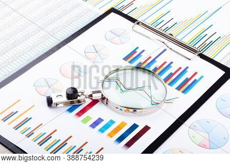 Magnifying Glass Lying On Business Charts And Graphs. Business Planning,accounting,analysis,financia