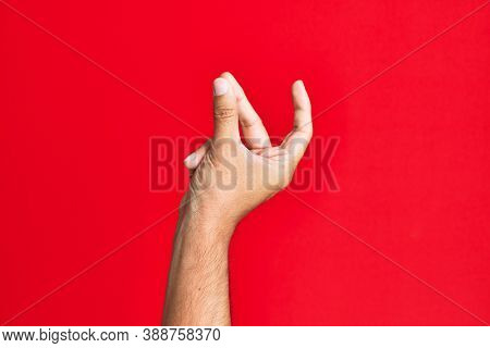 Arm of caucasian white young man over red isolated background snapping fingers for success, easy and click symbol gesture with hand