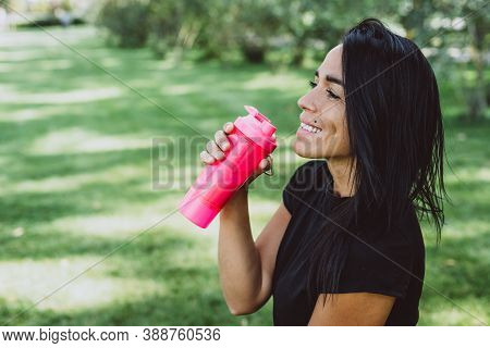 Young Fit Tanned Woman Athlete Drinks Protein Shake After Training Outdoors. Sports Nutrition. Soft