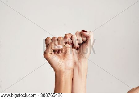 Close Up Of Two Female Hands Making A Pinkie Promise Sign Isolated Over Grey Background. The Symbol