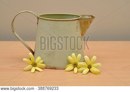 A Rusty Old Mug On A Table With Yellow Daisies