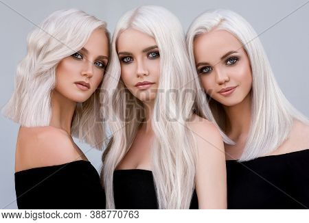 Three Beautiful Girls With Hair Coloring In Ultra Blond. Stylish Hairstyle Curls Done In A Beauty Sa