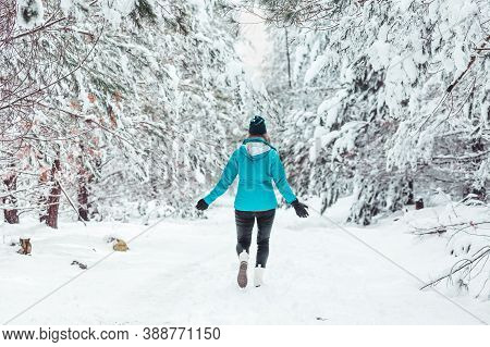 Woman Walking In A Snow Covered Forest With Snowflakes Falling