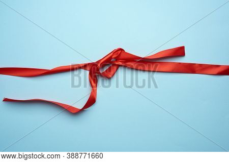 Curled Red Silk Ribbon On Blue Background, Top View