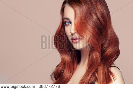 Beauty Redhead Girl With Long  And   Shiny Wavy Red Hair .  Beautiful   Woman Model With Curly Hairs