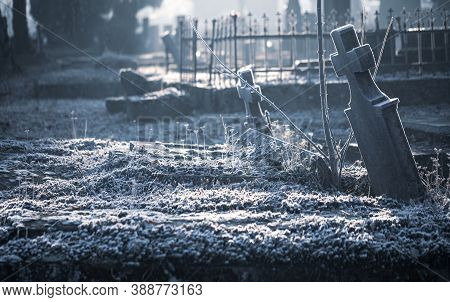 Old Cemetery Graveyard Tombstone Grave Cross Made Of Stone Or Marble Covered In Ice Frost On A Cold