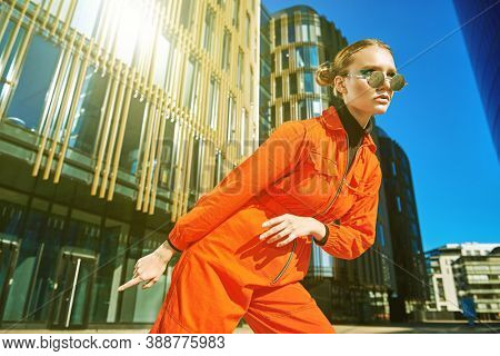 Bright youth style. Modern fashionable girl in bright orange jumpsuit and round sunglasses poses against the backdrop of skyscrapers.  Fashion shot.