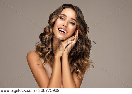 Beautiful Smiling Woman Holding Hands Near Face. Beauty Girl  With Curly Hair   . Presenting Your Pr